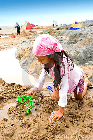 Young girl making sand castle
