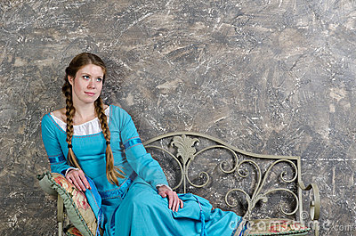Young girl in medieval dress sits on a banquette