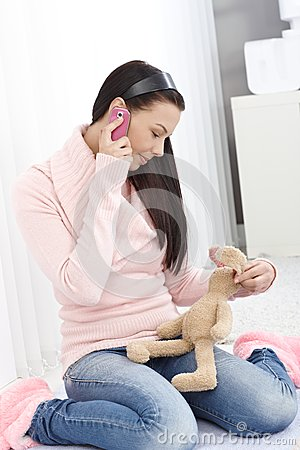 Young girl on mobile holding toy bunny