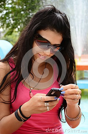Young girl  with mobile phone in th park