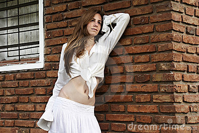 The young girl near a brick wall