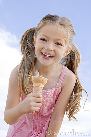 Young girl outdoors eating ice cream cone