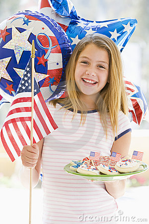 Young girl outdoors on fourth of July with flag