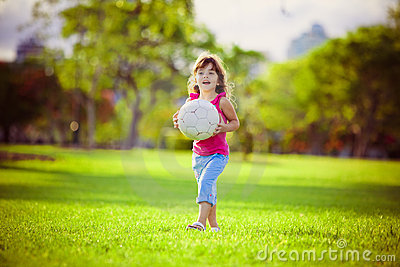 Young girl in the park holding white ball