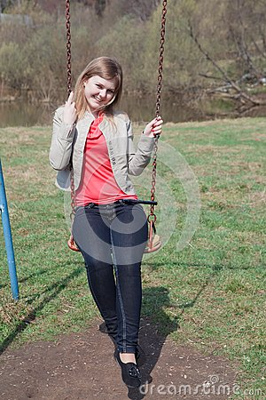 Young girl in the park sitting on the swing