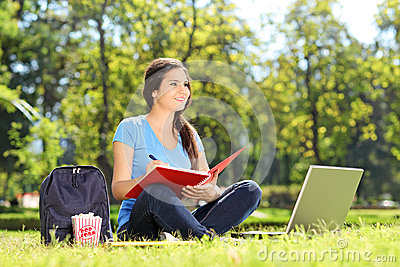 Young girl in park writing in a notebook