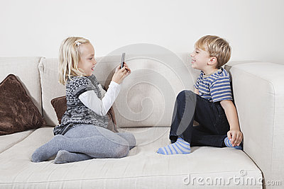 Young girl photographing brother through cell phone on sofa