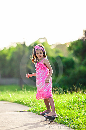 Young girl in pink dress riding on skateboard