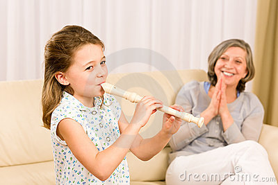 Young girl play flute with proud grandmother