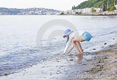 Young girl playing along the shore