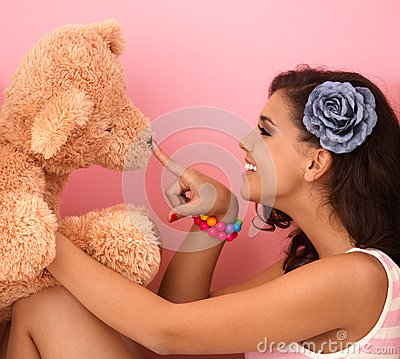 Young girl playing with big teddy bear