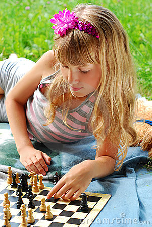 Young girl playing chess outside