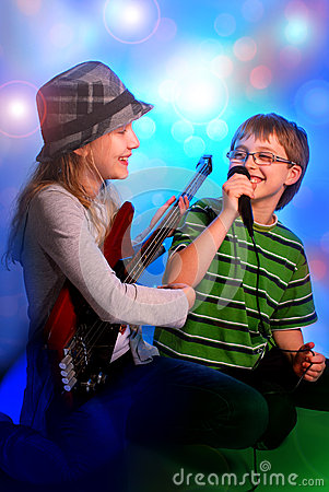 Young girl playing guitar and boy singing