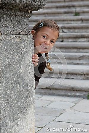 Young girl playing peek a boo