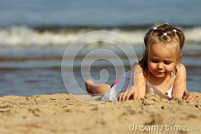 Young girl playing with sand o