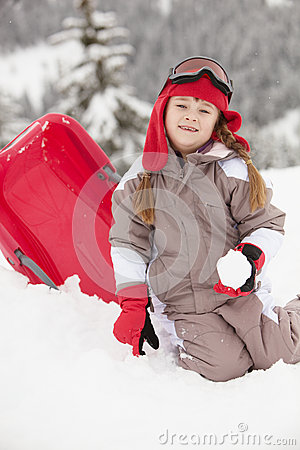Young Girl Playing With Sledge On Ski Holiday