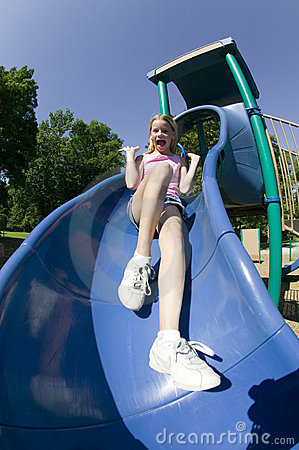 Young girl playing on a slide at the park