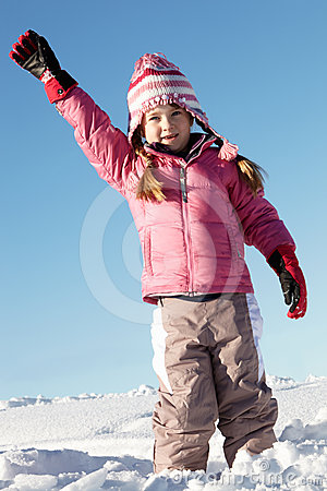 Young Girl Playing In Snow On Holiday In Mountains