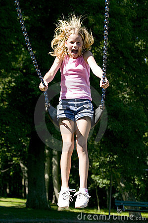 Young girl playing on a swing set at the park
