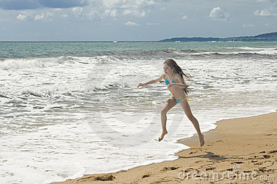 Young girl plays on the beach II