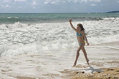 Young girl plays on the beach III