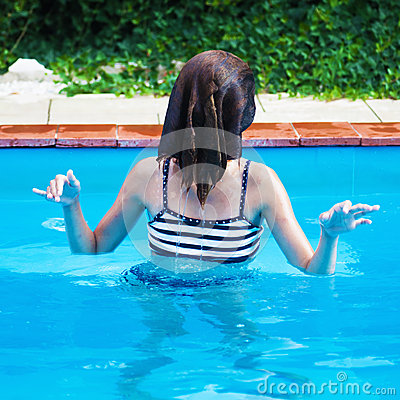 Young girl plays in a pool