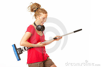 Young girl pretending to play the guitar on a mop