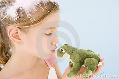 Young girl in princess costume kissing plush frog