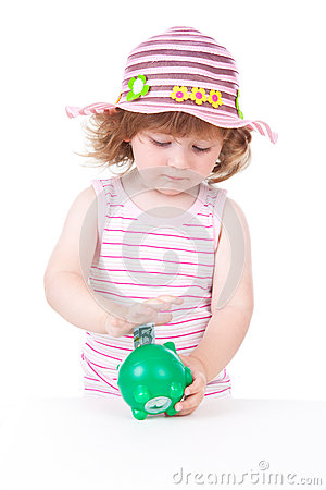 Young girl putting a euro note in her piggy bank