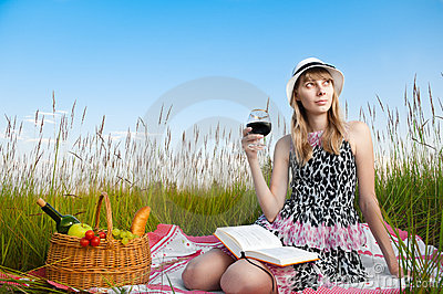Young girl reading book and drinking wine
