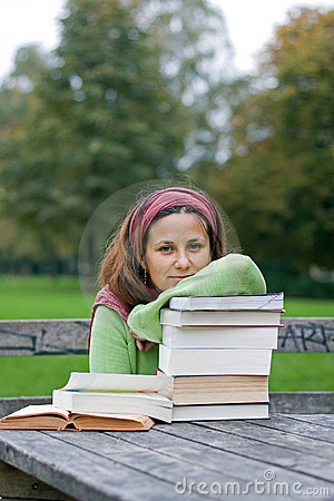Young girl reading a book in a park