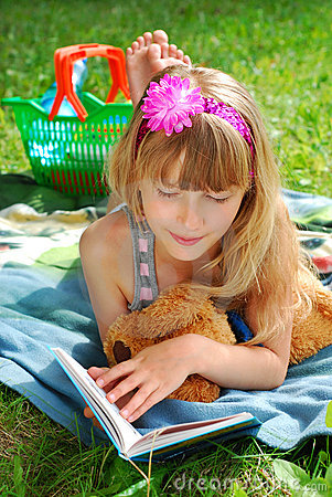 Young girl reading a book on the picnic