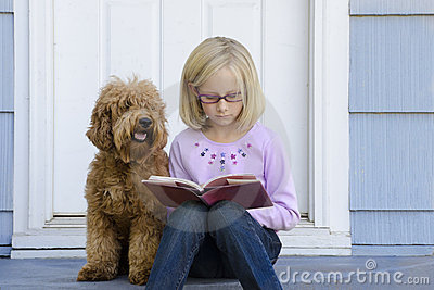 Young girl reading with dog