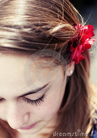 Young girl with red flower on her hair