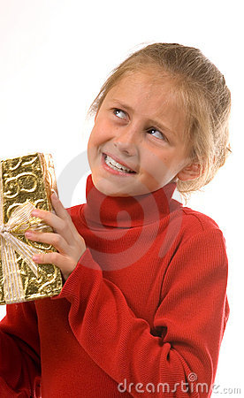 Young girl in red shaking gold Christmas present