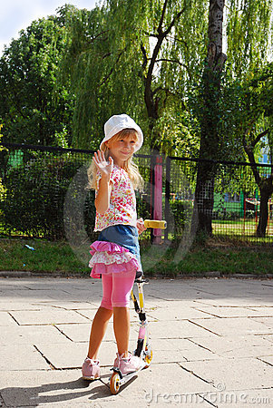 Young girl riding scooter  waving hand to friends