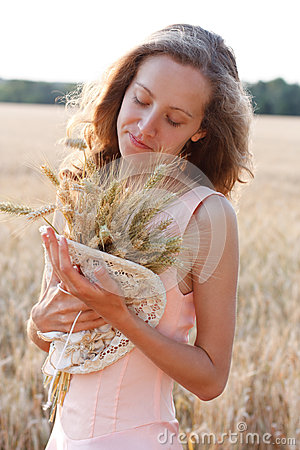 Young girl with ripe wheat ears in the hands