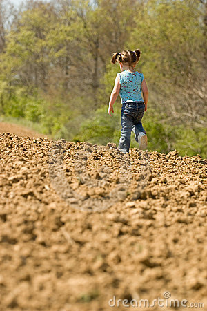 Young Girl Running on a Plowed Field