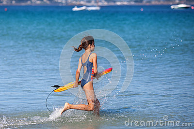 Young girl runs with her surfboard in the water