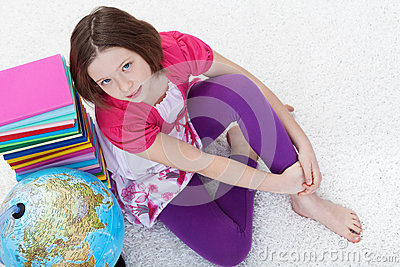 Young girl with school books and earth globe