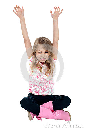 Young girl seated on floor posing with raised arms