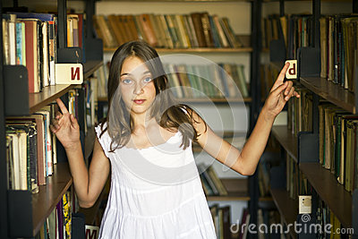 Young girl between shelves of old library