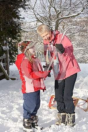 Young Girl Showing Grandmother Icicle In Snowy Lan