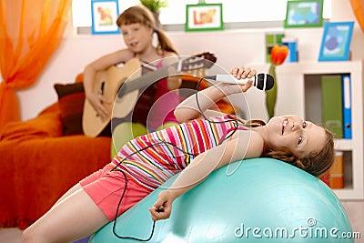 Young girl singing, posing on gym ball