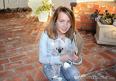 Young Girl Sits On Porch