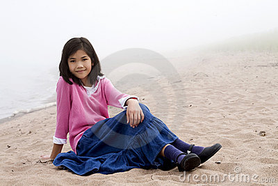 Young girl sitting on beach