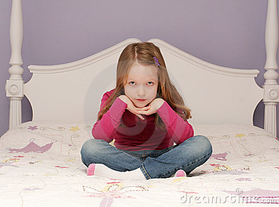Young girl sitting on bed