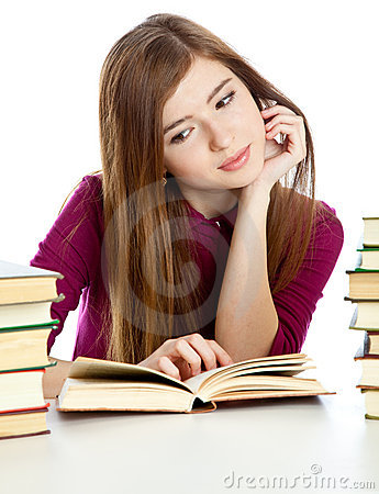 Young girl sitting at the desk and reading book.