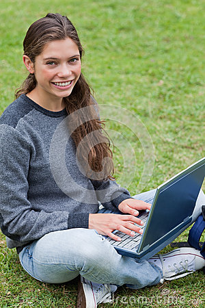 Young girl sitting down while using her laptop