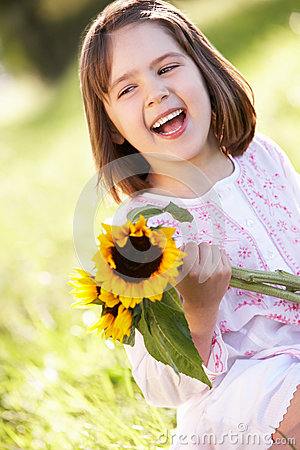 Young Girl Sitting In Field Holding Sunflower